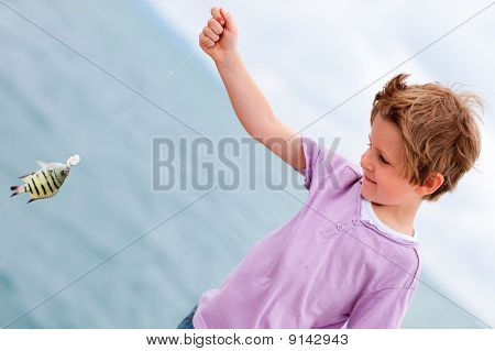 Happy boy holding small fish he just caught poster
