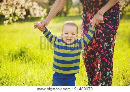 Baby Walking In Green Park Holding Hands Of Mother