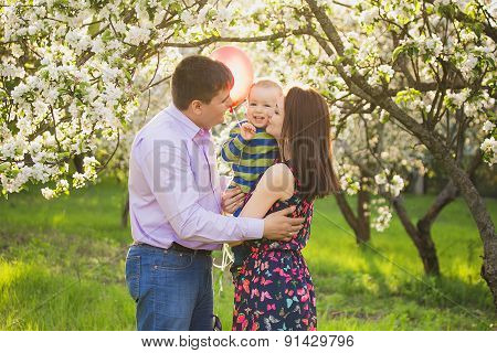 Portrait Of Happy Family. Father, Mother, Child Hugging And Kissing