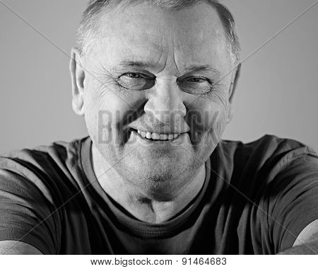 Black and white portrait of cheerful aged man in t-shirt smiling with dimples