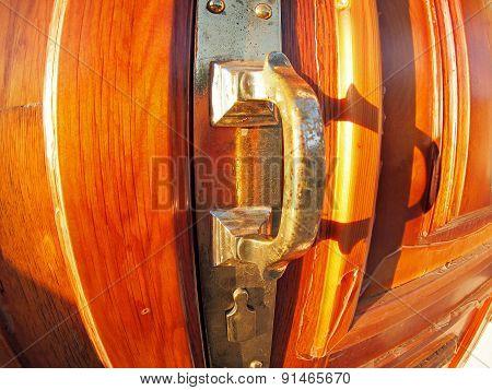 Old Bronze Door Handle Close-up On A Wooden Red Door