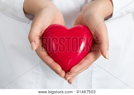 Female Doctors's Hands Holding And Covering Red Heart