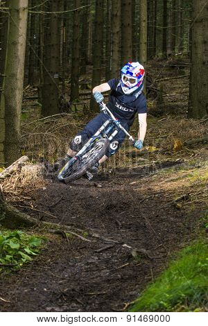 Downhill Biker Jumps Over A Ramp In The Forest