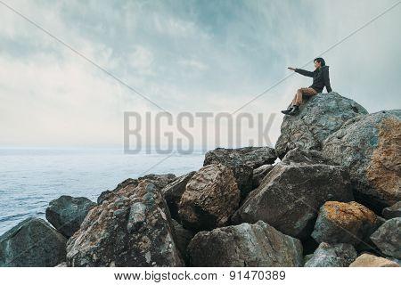 Woman Sitting On Stone Coast