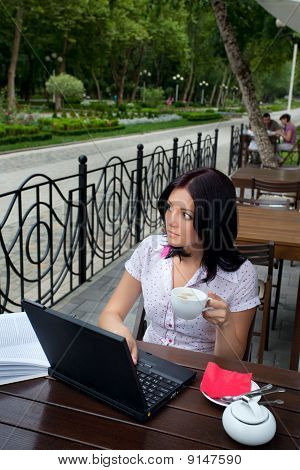 Girl With Laptop In Cafe
