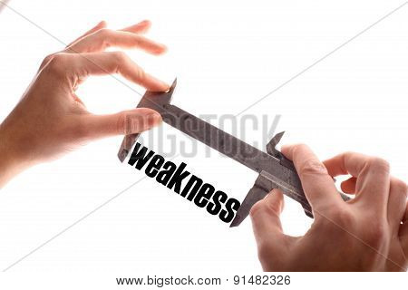 """Color horizontal shot of two hands holding a caliper and measuring the word """"weakness"""". poster"""
