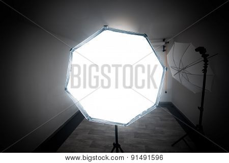 Deep octobox studio softbox modifier with studio umbrella in the back is shooting at the viewer in a professional photo studio. poster