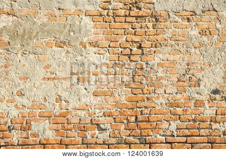 Old brick wall partly covered with plaster