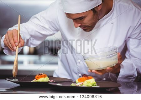 Chef putting sauce on a dish in a commercial kitchen