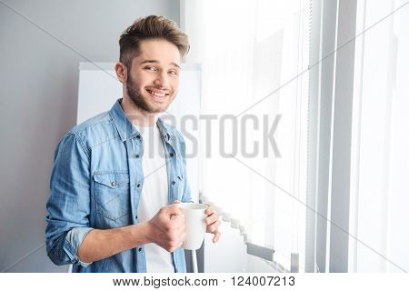 Deserve relaxation. Cheerful handsome man holding cup and drinking tea while having rest at work ** Note: Visible grain at 100%, best at smaller sizes