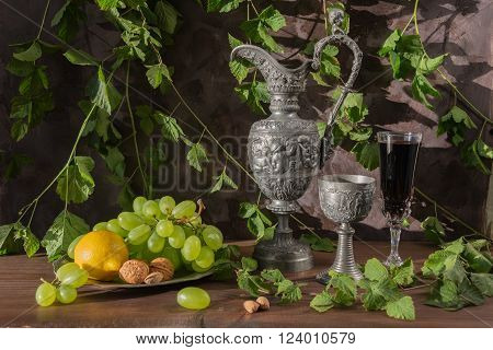 Still life in medieval style with antique pitcher and a goblets filled with red wine as well as walnuts green grapes and lemon on a dark background covered with green plants