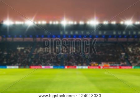 Blurry de-focused stadium football at twilight background.