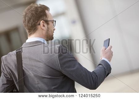 Businessman with the laptop bag over his shoulder using smart phone in the front of the business building. He is wearing suit and very satisfied.