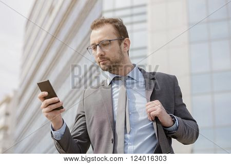 Businessman with the laptop bag over his shoulder using smart phone in the front of the business building. He is wearing suit and express satisfaction