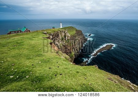 Landscape of Akraberg, southernmost point of Faroe Islands archipelago . Unspoilt nature with a lighthouse .