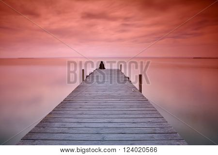 Unrecognizable person sitting on edge of wooden pier at sunset of red and violet colors
