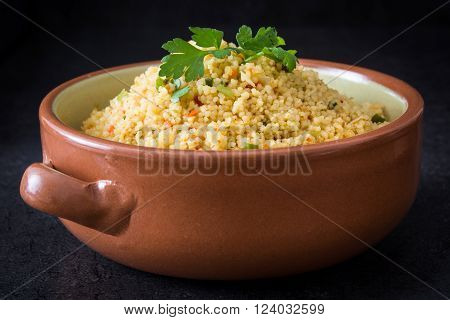 Homemade Couscous with vegetables on black stone