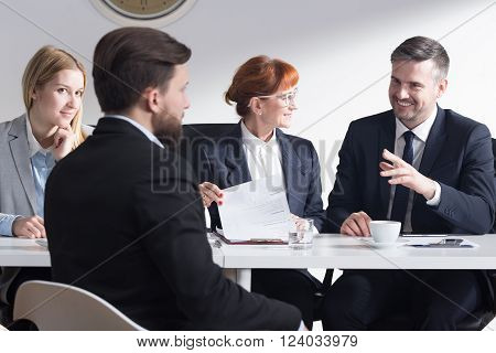 Handsome businessman joking with new applicant and other employers during job interviewHandsome businessman joking with new applicant and other employers during job interview