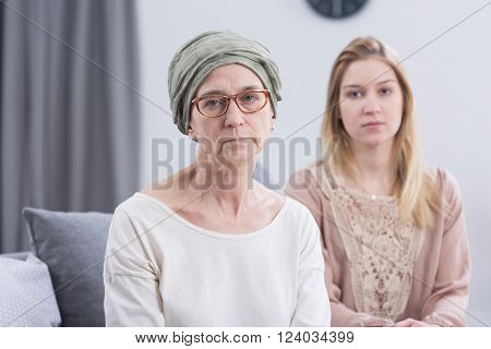 Senior worried woman with scarf on head with cancer and her supportive daughter