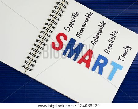 SMART Goals on blank notebook with blue paper background (Business Concept)