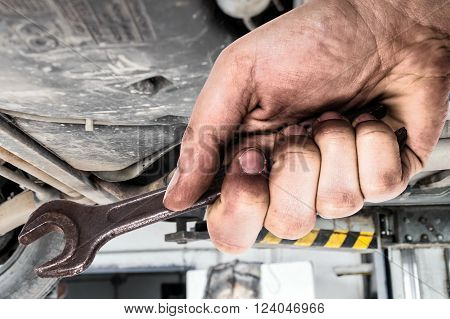 Dirty hand holding wrench. Car servis .