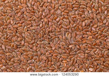 Closeup background texture photo of reddish brown seeds of Linseed, also called flaxseed. Flaxseed are seeds from flax plant