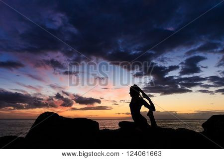Summer sunset yoga session on beautiful Playa Fanabe beach - tropical Tenerife island, Canary in Spain. Eka Pada Rajakapotasana - legged king pigeon pose