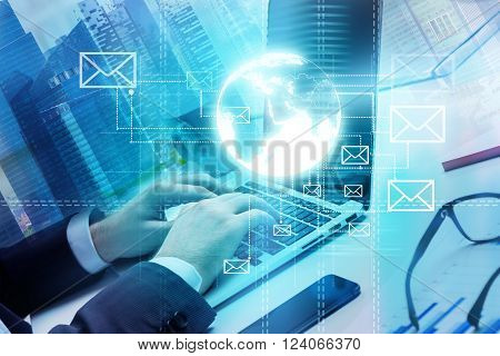 Businessman typing on laptop and sending emails smartphone and glasses on table. Only hands seen. Office buildings. Double exposure. Concept of work.