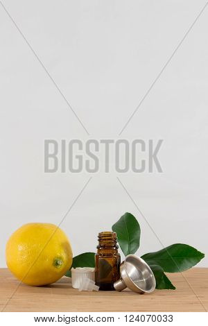 Lemon Essential Oil with Bottle,Funnel and Citrus Leaves poster