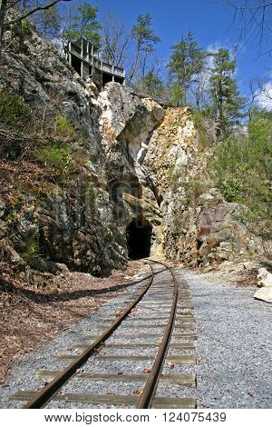a house sits on the ridge above railroad tracks going into a tunnel