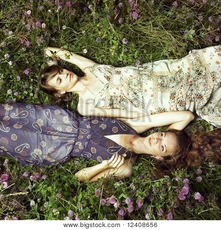 Two romantic girl lying on flower meadow