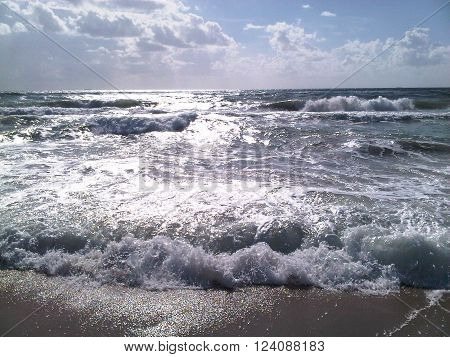Mediterranean beach during a windstorm, breaking waves and surf
