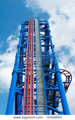 huge thrill ride to blue cloudy sky