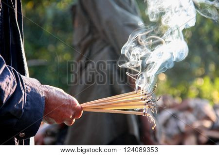 hand holding incense sticks for worship praying god of Asia religion ** Note: Soft Focus at 100%, best at smaller sizes
