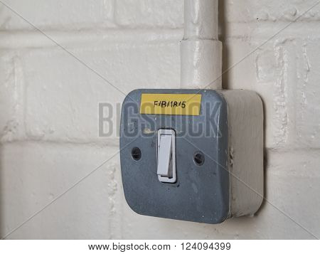 Light switch with exposed cable conduit on painted brick wall
