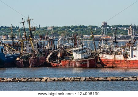 Montevideo, Uruguay - December 15, 2012: The abandoned old rusty ship in the Port of Montevideo, Uruguay at December 15, 2012. Montevideo in the background.