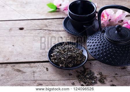 Green tea in bowl and traditional asian tea set on aged wooden background. Selective focus is on tea. Place for text.