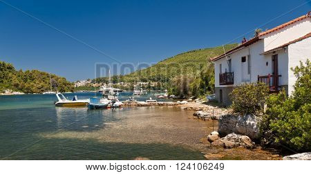 Calm sea bay with yachts boats and houses on Skopelos island in summer day