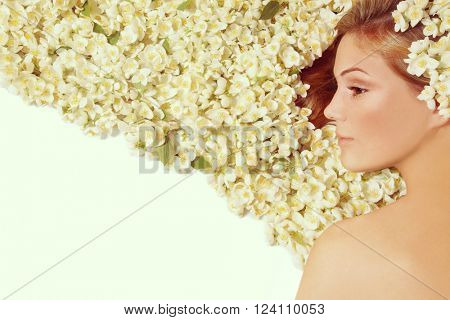 Vintage style profile portrait of young beautiful girl with clean sunny make-up and flowers in her long hair