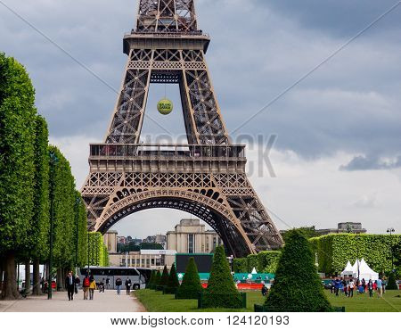 Paris, France May 26 2015: Eiffel Tower at time of French Open Tennis Tournament Roland Garros, tennis ball hanging from tower