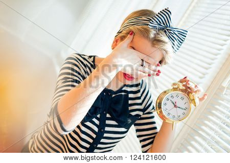 Portrait of a beautiful happy smiling young pinup woman showing alarm clock and hiding face in shame standing by the bright sunny window