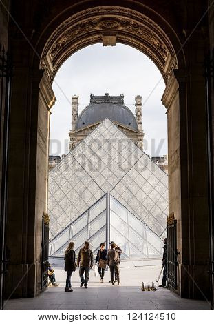 Paris, France May 26 2015: Archway to The Louvre with tourists and hawkers selling souvenirs