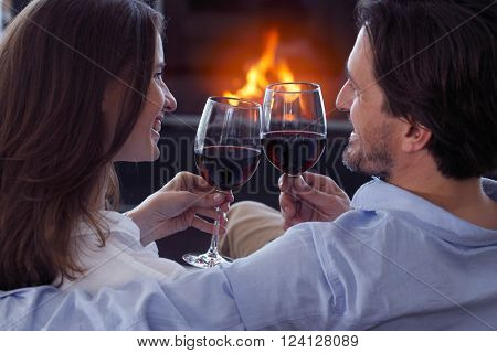 Romantic couple sitting next to fireplace with wine