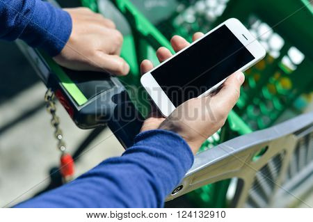 Cellphone and cart on store goods background. Closeup on person holding mobile smart phone in hand during shopping.