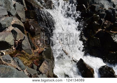 A waterfall flowing over rocks during the spring