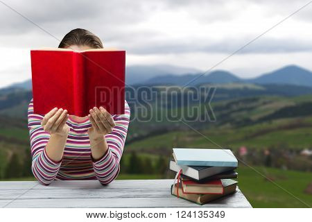 Young woman reading a book and covering her face , sitting by wooden table with stack of colorful hardback books on blurred nature landscape backdrop