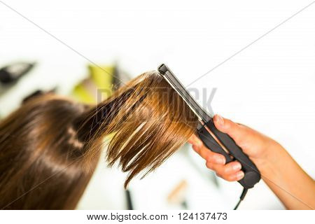 Close-up of a hairdresser straightening long blonde hair with hair irons. ** Note: Shallow depth of field