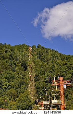 An empty  sky Lift is capable of transporting tourists to the summit of a mountain which looks over the valley of Gatlinburg, Tennesse