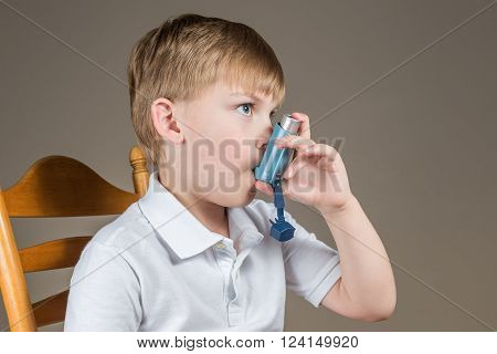 Young blonde-haired asthmatic boy using a blue inhaler.