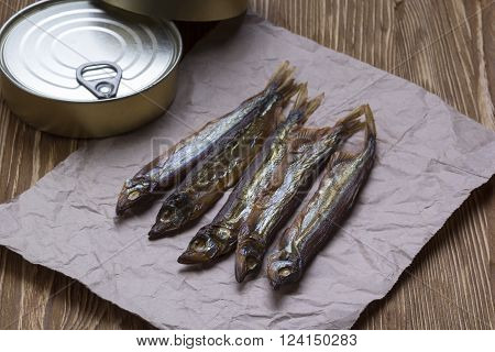 Smoked capelin and conserve tins on brown  wooden background poster